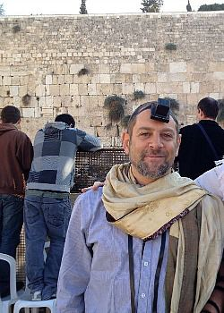 Amichai Lau-Lavie at the Western Wall wearing his tallit like a scarf.