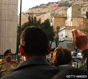 RAID RAGE: Syrian police guard the American embassy in Damascus as protesters demonstrate in the wake of an American military raid on a Syrian border town.