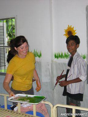 ARTSY: Erin and Sambo work on a mural at the Kampong Chhnang orphanage.