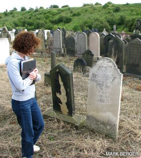 ANCESTRAL TIES: Jane Eisner visits a weathered tombstone in an English graveyard that family legend says belongs to a distant relative. Below, first stop on the visit was to the grave of Rose Levy, her maternal great-grandmother.
