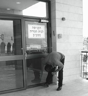 On the Job: A municipal employee in Ma?ale Adumim in the West Bank cleans a set of glass doors.