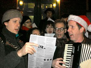 Merry Hanukkah?: Doug Nervik (holding an accordion) has led a group of Christmas carolers ? some of whom are Jewish ? through the streets of Manhattan?s East Village every winter for more than a quarter century.