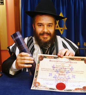 AUTHENTIC: Rabbi Mendel Jacobs displays a certificate from the Scottish Tartans Authority and a piece of fabric featuring the design of the first official Jewish Tartan.