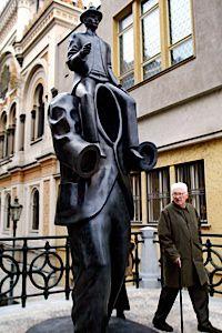 Fill The Void: A passerby contemplates a sculpture of Franz Kafka in Prague.