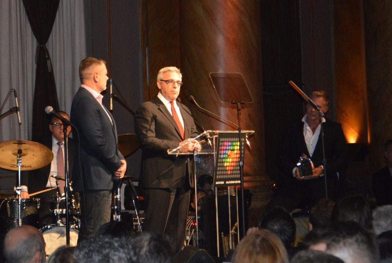 Mitchell Gold (C) speaks at Friday's Ali Forney Center gala as business partner Bob Williams (L) and weather guru Sam Champion (R), holding award, listen.