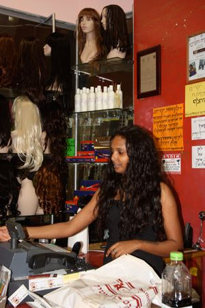 **A Place Of Refuge: An African woman works at a hair exten- sion shop in the bus station mall, a place where many of the refugees find work.