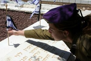 Israeli soldier lays flower at grave on Yom Hazikaron, the country?s memorial day.