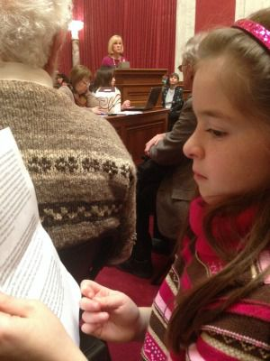 Ava Rose Katz, 7, reads testimony as her father prepares to testify at a West Virginia hearing into the Elk River chemical spill.
