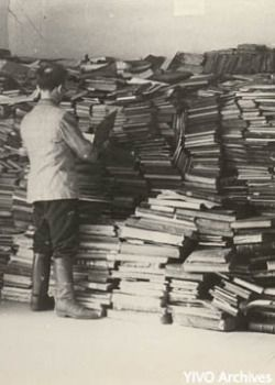 Scattered Records: Shmerke Kaczerginski sorts through Jewish books in the YIVO building in Vilna during World War II. Until the Holocaust, the city was a center of Jewish culture.