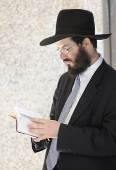 Abuse: Rabbi Yaakov Weiss, son-in-law of Sholom Rubashkin, prays while awaiting an appearance in an Albany police court.